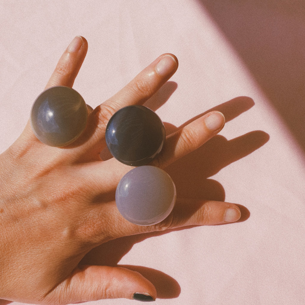 Hand holding three Grey Agate mushrooms between fingers