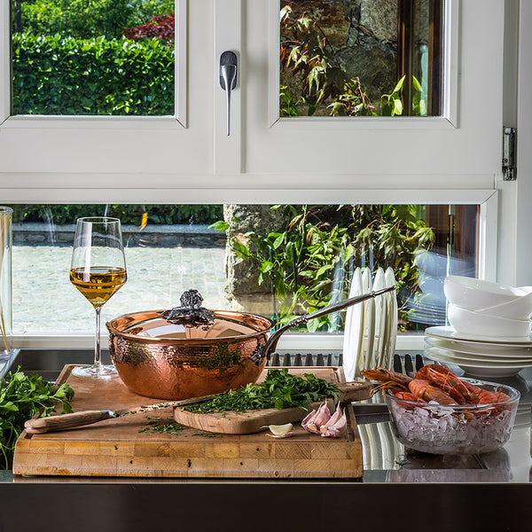 Hand-hammered, copper chef pan with stainless steel lining in the kitchen with chopped herbs and shellfish