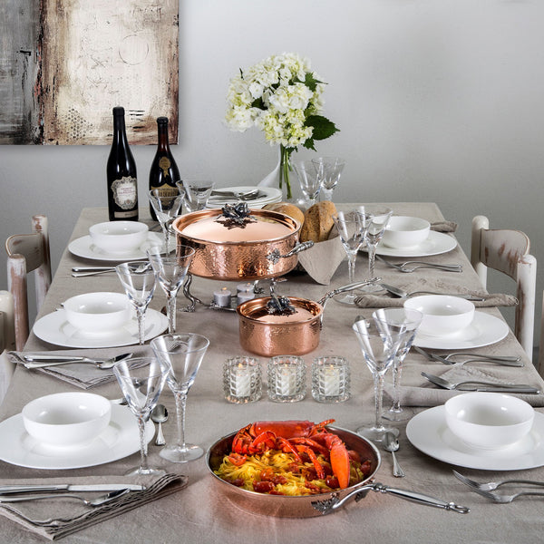 Table set for family meal complete with copper cookware set, seafood pasta, and wine.