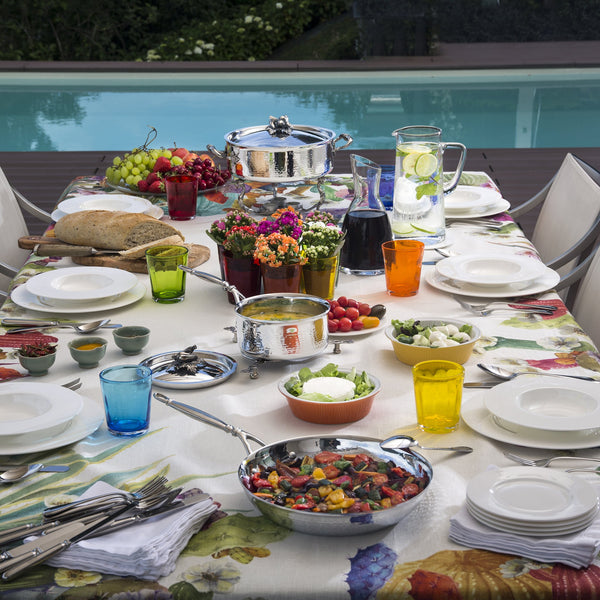 Poolside meal set with hand-hammered clad stainless steel cookware filled with soups, breads, and veggies