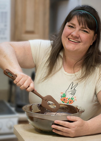 Becca Larson, owner of Pyroclastic Chocolate, stirs a bowl of chocolate in her kitchen
