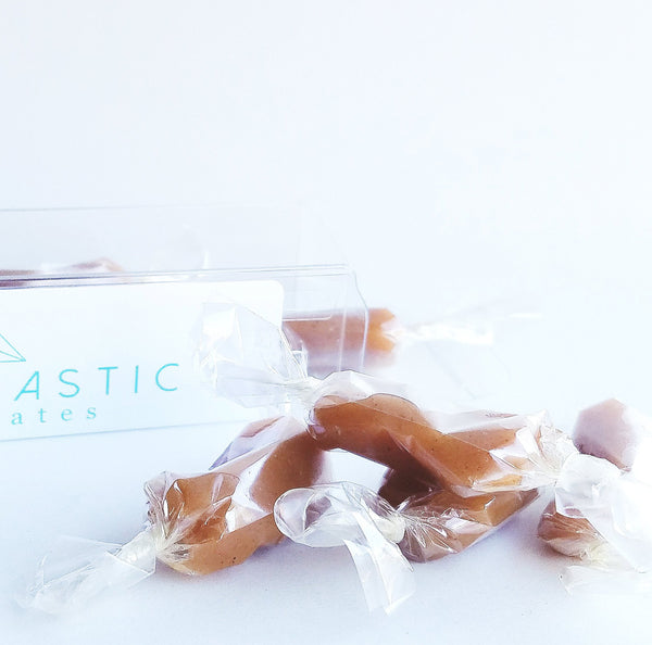 Apple Cider Caramels sit haphazardly in front of their open box on a white background.