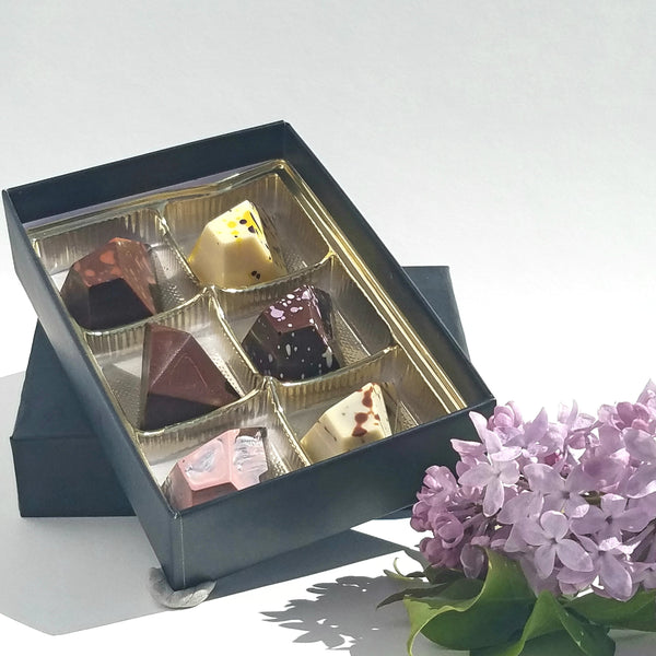 six piece box of truffles from pyroclastic chocolates. black box with gold tray. shown with lilac flowers