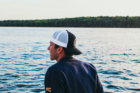 Man wearing the Seven Forty Six Logo snap-back hat in black and white