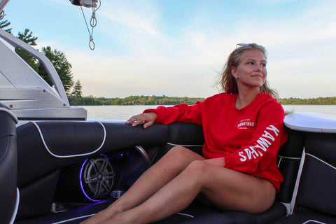 Woman sitting in a boat on Balsam Lakes in Seven Forty Six's Red Kawarthas Crewneck