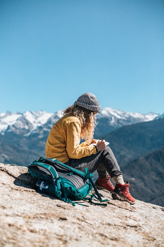 Woman writing in a journal on the top of a mountain
