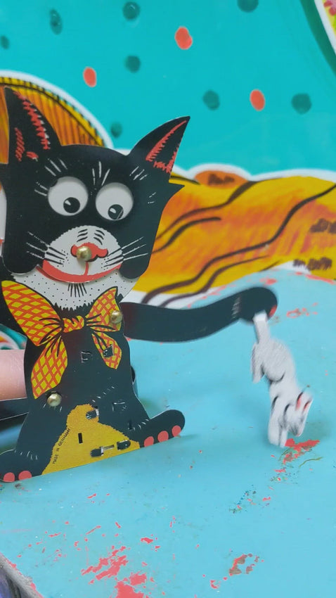 This cheeky tin toy cat is having such a time with a rabbit he has caught.