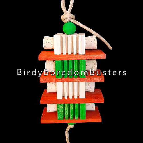 Christmas colored notched pine blocks with cork stoppers inserted into the sides with softwood pine slats strung on paper rope. Contains no metal parts. Designed for intermediate sized birds.  Measures approx 3-1/2