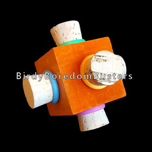 "Corks with rubber rings stuffed into each side of a brightly colored pine cube. Designed for medium and large birds.  Measures approx 2-1/2""."