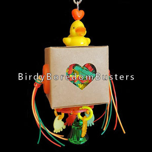 "A little duck sitting atop a box stuffed with paper shred with non-toxic plastic lacing to nibble. Under the box is a wheel with charms to rattle and a bell to ring. Stuff the box with treats for more foraging fun.  Hangs approx 6-1/2"" including link (box is 2"" x 2"" x 2"")"