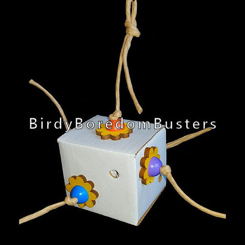 A 3 inch cardboard kraft paper box trimmed with pine daisies and chewy plastic beads on paper rope. The box is filled with crinkle paper and will be enjoyed by birds of all sizes.  Hangs approx 11