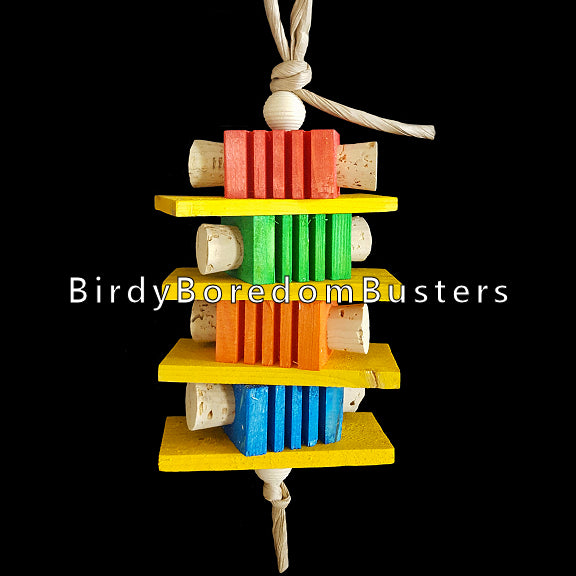 Four brightly colored notched pine blocks with cork stoppers inserted into the sides with four softwood slats and wood beads all strung on paper rope. Contains no metal parts.  Measures approx 3-1/2