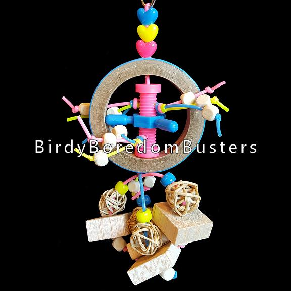 Little wood beads streaming out of a plastic bolt inside a birdie bagel with munch balls, balsa blocks & beads. Contains no metal parts.   Measures approx 3