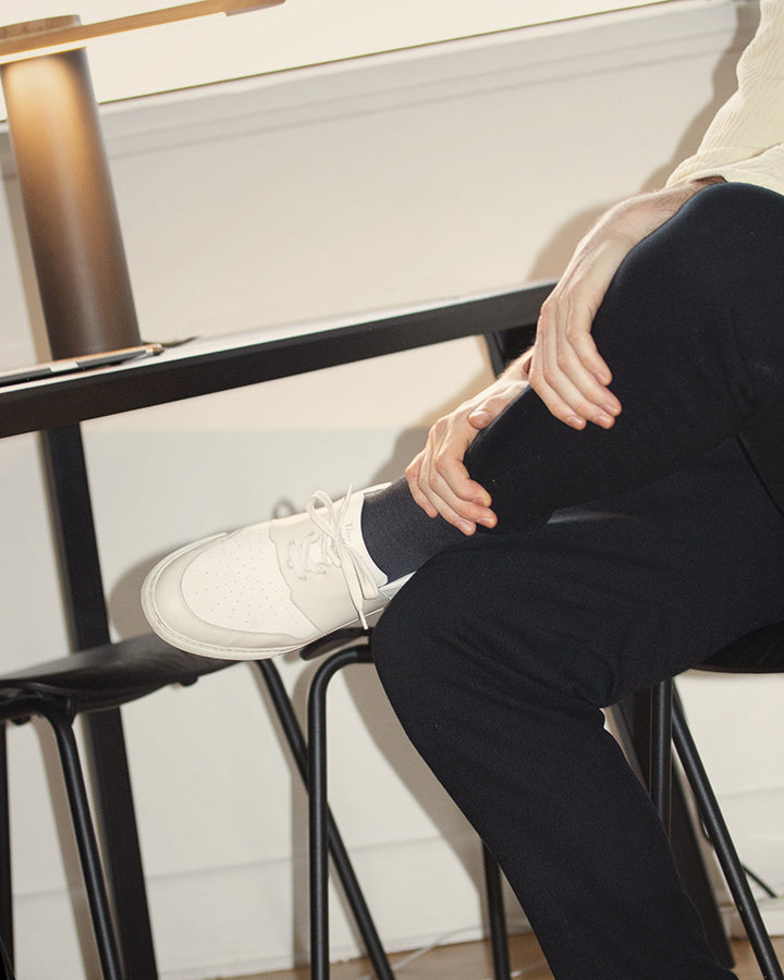 pyla-vanilla-sneakers-worn-by-etienne-delorme-sitting-on-a-chair-with-legs-crossed-big-size-picture