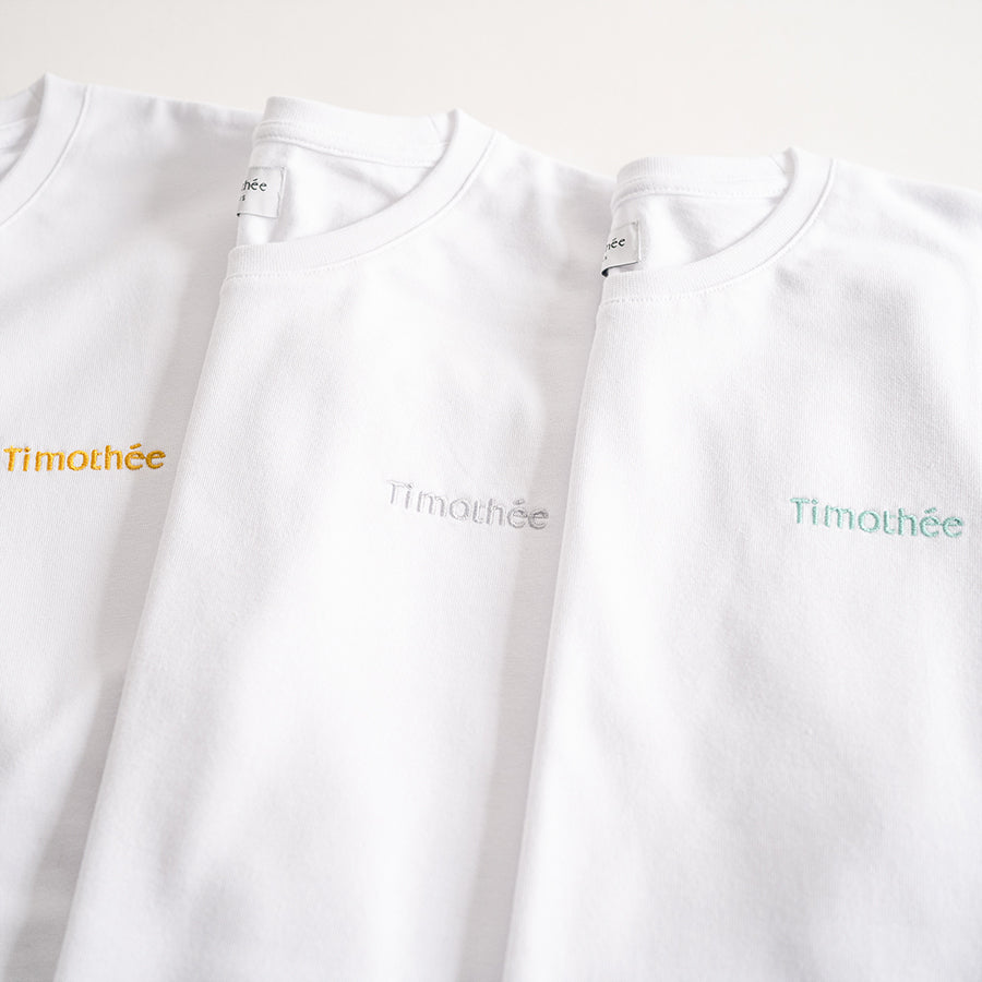 white-short-sleeve-embroidered-timothee-paris-logo-on-chest-oversized-tshirt-gold-silver-green-close-up