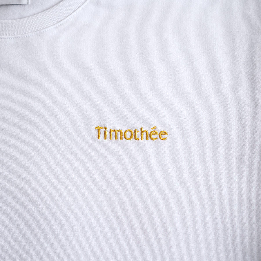 white-short-sleeve-embroidered-timothee-paris-logo-on-chest-oversized-tshirt-close-up-honey-gold