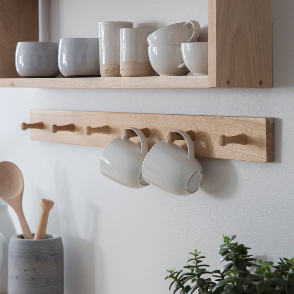 oak peg rail featuring two mugs hanging on it