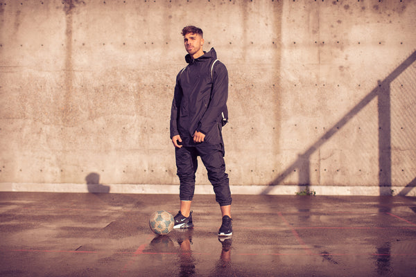 After editing - Man in a black windbreaker outfit with a soccer ball