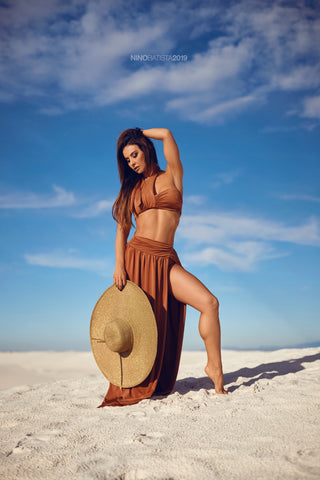 Model outdoors in the sand holding a sunhat