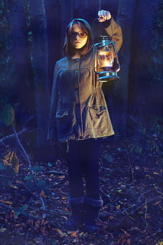 Photograph of a girl holding a lantern out of doors in the evening