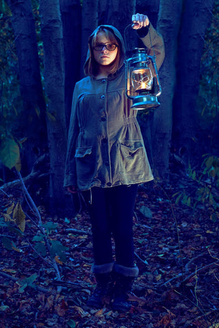 Color graded image of a girl holding a lamp outdoors