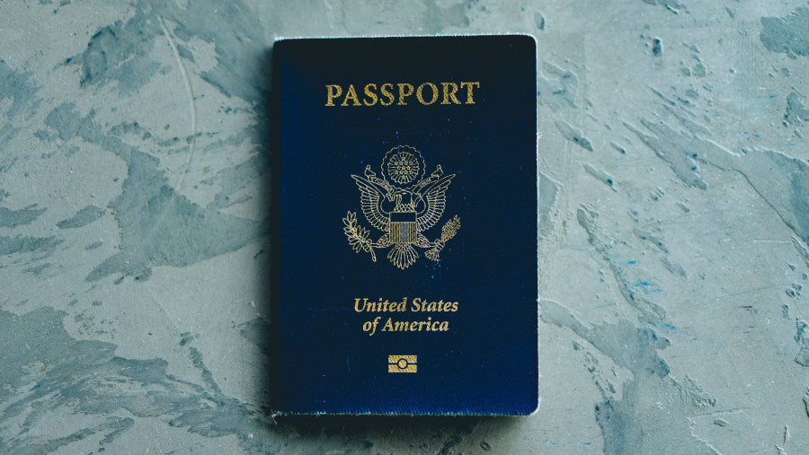 a U.S. passport lies on a blue surface