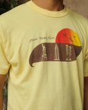 Shown up close, a light yellow colored vintage t-shirt featuring classy text that spells out New York City over a brown solid color swish that has cut out pictures of the Statue of Liberty, the Eiffel Tower, and the twin towers (never forget!). Above that there are brown birds over a half circle that is filled with a red to yellow gradient.
