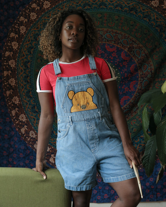 These light wash blue denim overall shorts feature a design of Winnie the Pooh's face on the bib pocket. You can see the top half of his face as if he were peeking out. There are belt loops on the waist, a bib pocket, and two front pockets pictured.