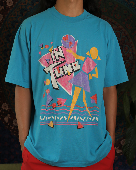 Bright blue t-shirt that says In Tune with colorful geometric shapes. Shows a figure holding the earth in yellow, pink, purple, and white colors. The design looks very 80s!