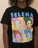 Close up of a model wearing a black t-shirt. The graphic on the T-shirt says Selena in light blue bold capital letters. Underneath is a four square repeating photo of Selena's face in alternating bright colors. Reminiscent of Andy Warhol.
