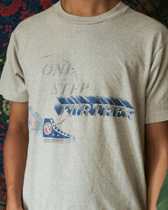 Model wears a light gray t-shirt with a graphic design. One step further is written in all capital letters in a darker gray. The word further has a blue shadow behind it. There are blue repeating high top tennis shoes on the bottom left of the letters.