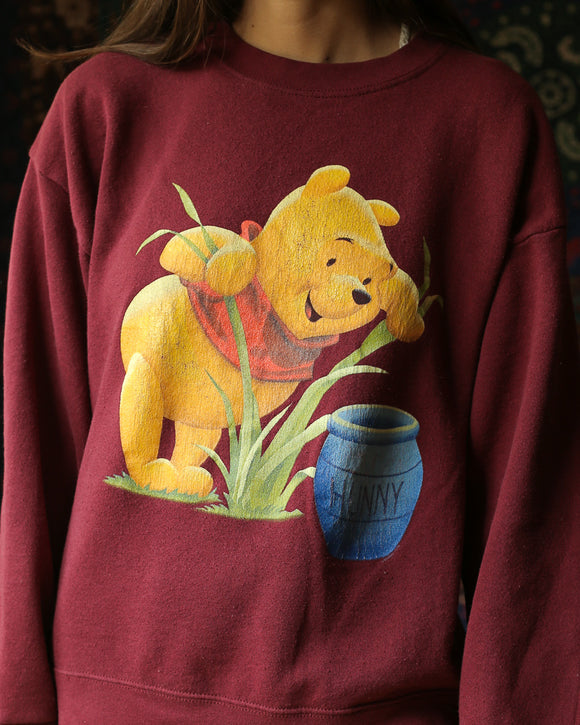 Close up of a maroon sweatshirt featuring Winnie the Pooh. The graphic shows Pooh bear looking through blades of grass at his blue hunny jar. The print is slightly cracked. The graphic takes up most of the chest. This item is vintage.