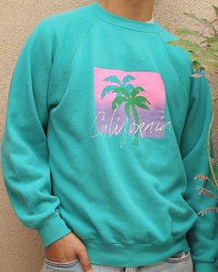 "This perfectly 80s vintage pullover sweatshirt is a mint green color featuring a double palm tree image behind the word ""California"" written in white cursive letters. These images sit on top of a pink to purple gradient (that looks like a sunset) covered in linear dots."