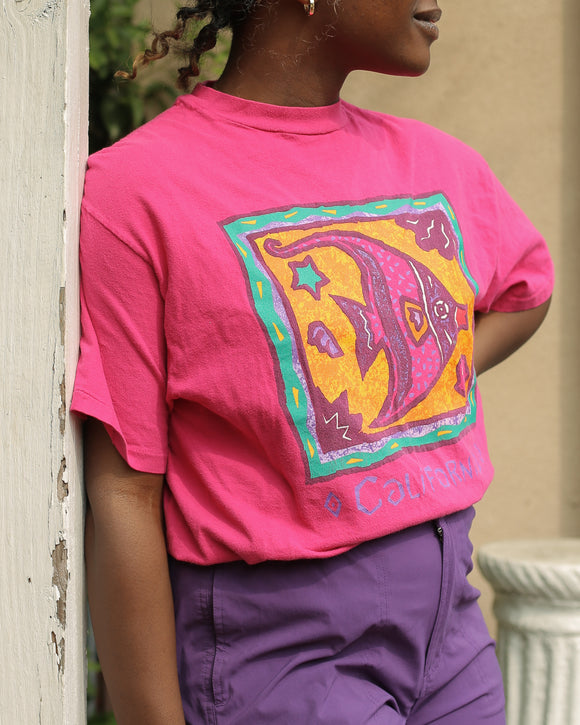 Model is wearing a pink shirt with a graphic design that features an artistic colorful painted drawing of a framed fish. Underneath it says California in funky purple letters.