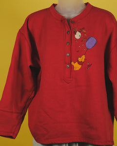 This red half button down henley sweatshirt is embroidered with a  winnie the pooh theme. Pooh hangs from a purple balloon above a bee hive. There are fall leaves surrounding the scene. The embroidery is to the right of the buttons.