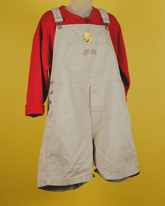 Tweety bird themed Khaki overall shorts. The bib pocket has an embroidered picture of tweety bird. Features adjustable straps, 3 button side closure, and two side pockets in the shorts.