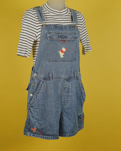 Light wash denim overalls with a bib velcro pocket featuring an embroidered picture of Winnie the Pooh. There is a butterfly on his nose. There is an embroidered butterfly on the bottom left of the shorts. There is another velcro pocket on the right short. 3 button closures on each side. 2 pockets on each side of the shorts.