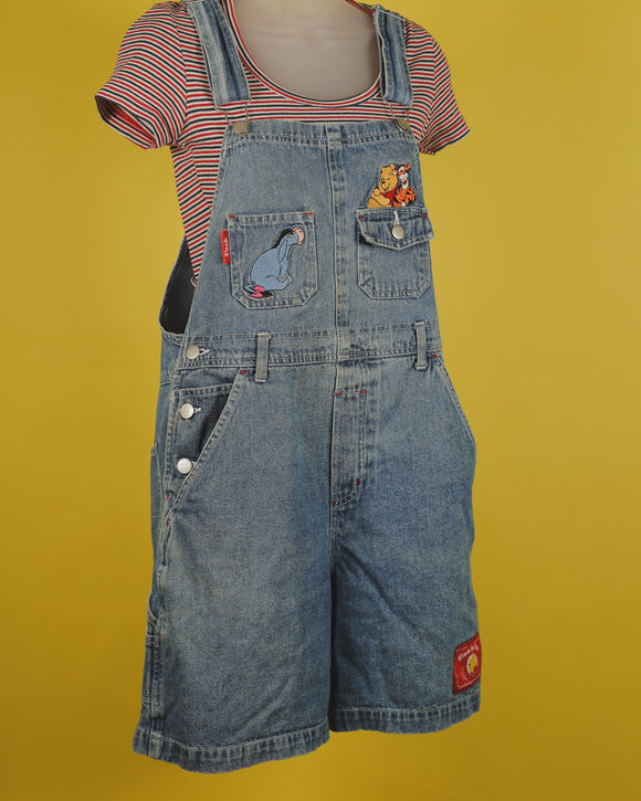 Denim overalls featuring two bib pockets with embroidered pictures of Eeyore, Tigger, and Pooh. There are 3 button closures on each side with two pockets in the shorts. There is a cute label tag on the right bottom side of the shorts. There are adjustable straps.