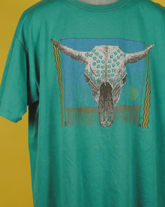 Close up of teal colored t-shirt. The design features a bull skull over a desert landscape. There are brown and yellow squiggly lines on each side. The landscape has a sun, a blue sky, some cactus, and dirt.