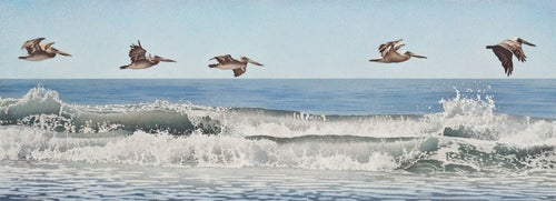 Five brown pelicans flying in formation above the breaking waves, pale blue sky and deeper blue ocean with white and gray toned waves