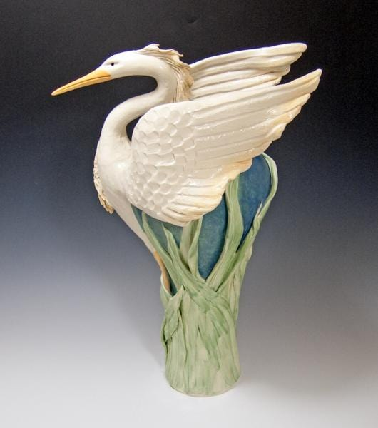 White preying heron with wings back, yellow beak, on green reed covered vase in soft teal.