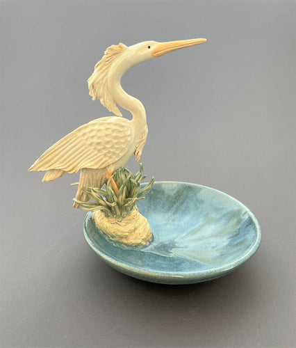 Creamy white graceful heron perched in the reeds, on the edge of a green blue bowl