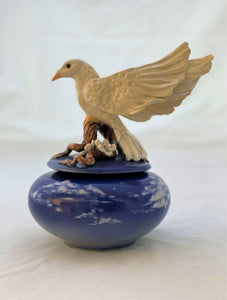 White dove atop a blossoming branch on a twilight blue jar  with clouds