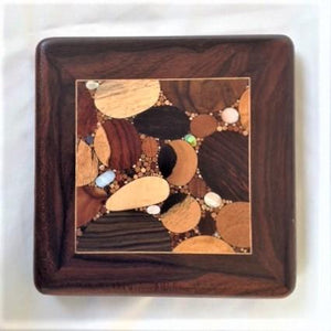 Various woods and shell inlaid into a small square, framed with deep dark wood and a thin pale inlaid line surrounding.