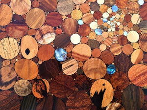 Over 100 kinds of wood and shell in a kaleidoscope effect of the big bang, detail of wood inlaid wall art piece.