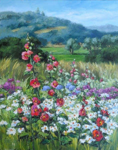 A profusion of blooms, pink-red hollyhocks, white and yellow daisies, with touches of blue and purple, and looking back to green fields and gentle hills.