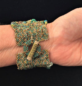 textural beaded cuff bracelet in greens, turquoise and golds, ring and post closure