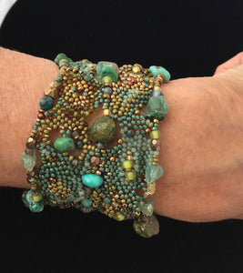 textural beaded cuff bracelet in greens, turquoise and golds, front view