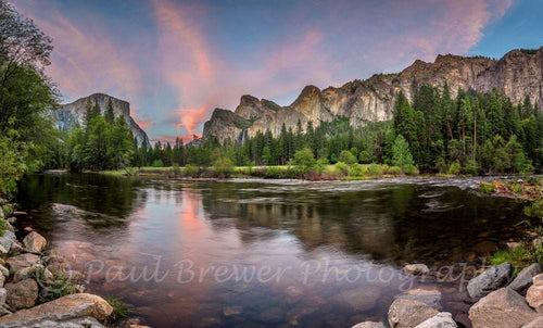 Iconic Yosemite Valley with the Merced River in the foreground and salmon pink clouds at sunset.