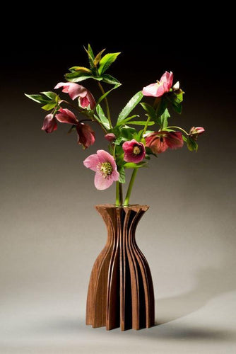 Jasmine vase of walnut, one piece of wood cut and opened to create a graceful form. With glass tube for water and flowers.